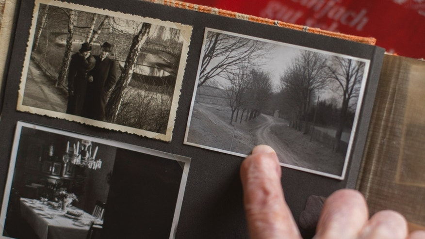 April 25, 2013 -  Woelk, one of Adolf Hitler's food testers, shows a photo album and points to a picture taken prior to WWII, showing the way to the later built Fuehrer Headquarters.