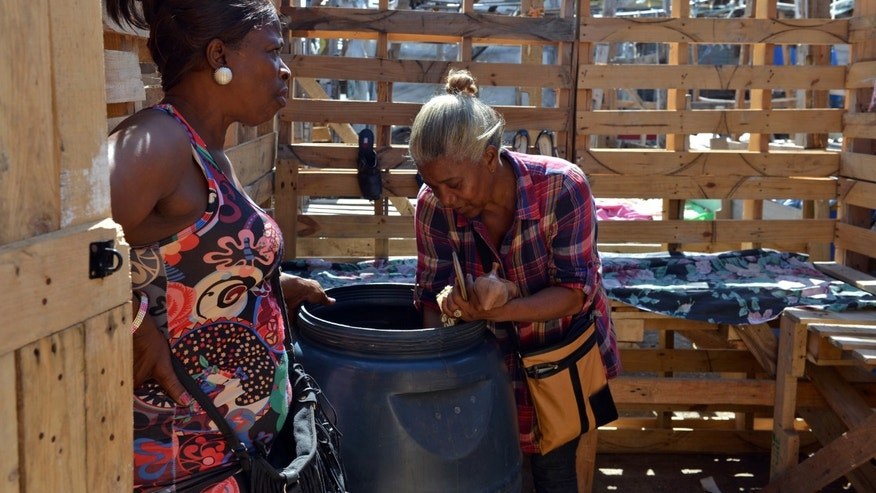 In this April 13, 2013 photo, Claudette Johnson, right, is accompanied by a friend while unpacking used clothing to sell at her stall at an outdoor market in West Kingston, Jamaica.   Johnson still has a hard time sleeping at night a decade after her son was fatally shot in a confrontation with Jamaican police and 15 years after her taxi driver husband was murdered by gunmen. Year after year, both cases have collected dust in the island's gridlocked court system, leaving her in limbo. (AP Photo/David McFadden)