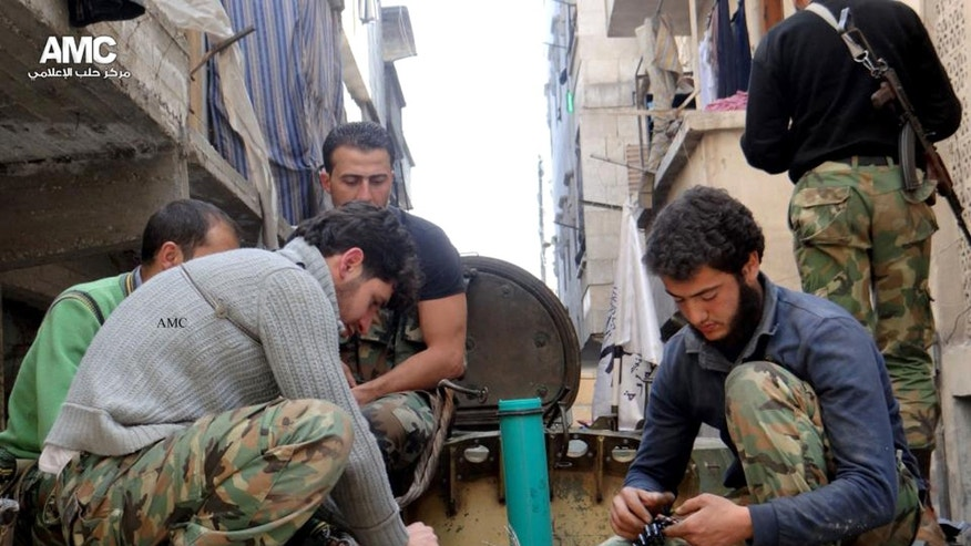 This citizen journalism image taken on Thursday, April 25, 2013 and provided by Aleppo Media Center AMC which has been authenticated based on its contents and other AP reporting, shows members of the free Syrian Army preparing their weapons, in the neighborhood of al-Amerieh in Aleppo, Syria. The White House disclosure on Thursday that the Syrian government has twice used chemical weapons still leaves the Obama administration stuck with a limited choice of military options to help the rebels oust President Bashar Assad. (AP Photo/Aleppo Media Center AMC)