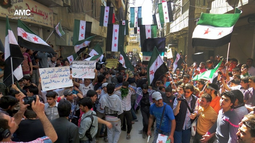 "This citizen journalism image provided by Aleppo Media Center AMC which has been authenticated based on its contents and other AP reporting, shows anti Syrian regime protesters holding banners and waving the Syrian revolutionary flags during a demonstration, in Aleppo, Syria, Friday, April 26, 2013. Araboc on banners read: ""we call upon the Free Syrian Army brigades and the Mujahedeen to stop the military convoy in the city of al-Safira,"" left, and ""all what Kerry has is the laughing cow cheese .""(AP Photo/Aleppo Media Center AMC)"