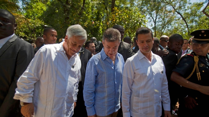 Chile's President Sebastian Pinera, left, Colombia's President Juan Manuel Santos, center, and Mexico's President Enrique Pena Nieto stroll through a hotel garden while taking a break from the  Association of Caribbean States regional summit, in Port-au-Prince, Haiti. Friday April 26, 2013. Haiti wrapped up the international summit on Friday that brought together six presidents from the region who all signed an agreement that called for an end to the U.S. embargo against Cuba and to help the region better prepare for disasters. (AP Photo/Dieu Nalio Chery)