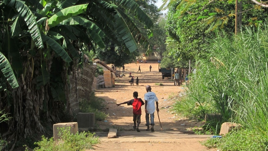 In this Thursday, April 11, 2013 photo, children walk along a street in the town of Ndele, Central African Republic. Townspeople who already have endured years of upheaval and rebellion are now confronting an increasingly complex array of armed fighters. (AP Photo/Krista Larson)