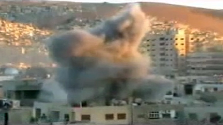 This image taken from video obtained from Ugarit, which has been authenticated based on its contents and other AP reporting, shows an explosion during heavy fighting between rebels and Syrian government forces in the Barzeh district of Damascus, Syria, Friday, April 26, 2013. On the streets of Damascus, the two-year old conflict dragged on Friday, with government troops pushing into two northern neighborhoods, triggering heavy fighting with rebels as they tried to advance under air and artillery support, activists said. The Britain-based Syrian Observatory for Human Rights said the fighting between rebels and soldiers backed by pro-government militiamen was concentrated in the Jobar and Barzeh areas.(AP Photo/Ugarit via AP video)