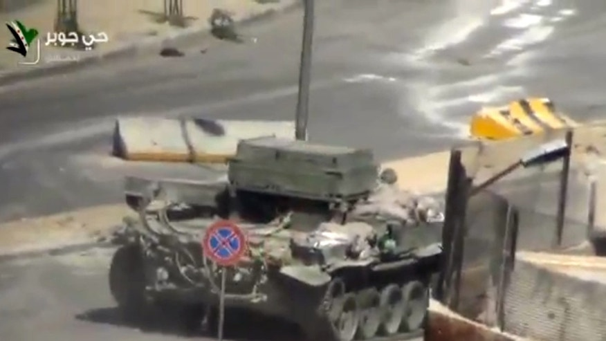This image taken from video obtained from Ugarit, which has been authenticated based on its contents and other AP reporting, shows a Syrian Army tank in the streets of the Jobar district of Damascus, Syria, Friday, April 26, 2013. On the streets of Damascus, the two-year old conflict dragged on Friday, with government troops pushing into two northern neighborhoods, triggering heavy fighting with rebels as they tried to advance under air and artillery support, activists said. The Britain-based Syrian Observatory for Human Rights said the fighting between rebels and soldiers backed by pro-government militiamen was concentrated in the Jobar and Barzeh areas.(AP Photo/Ugarit via AP video)