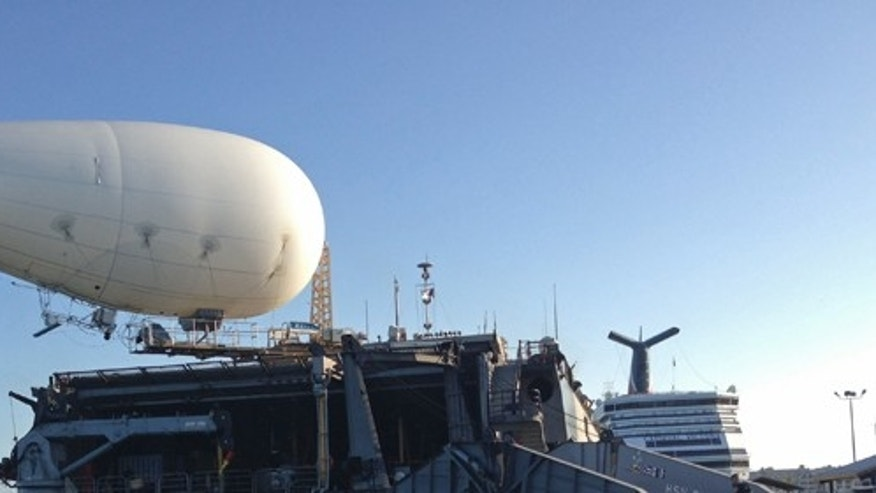 A balloon-like craft known as an aerostat is shown attached to the back of the U.S. Navy high speed vessel Swift docked in Key West, Florida, Friday, April 26, 2013. The U.S. Navy on Friday began testing two new aerial tools, borrowed from the battlefields of Afghanistan and Iraq, that officials say will make it easier to detect, track and videotape drug smugglers in action. (AP Photo/Ben Fox)
