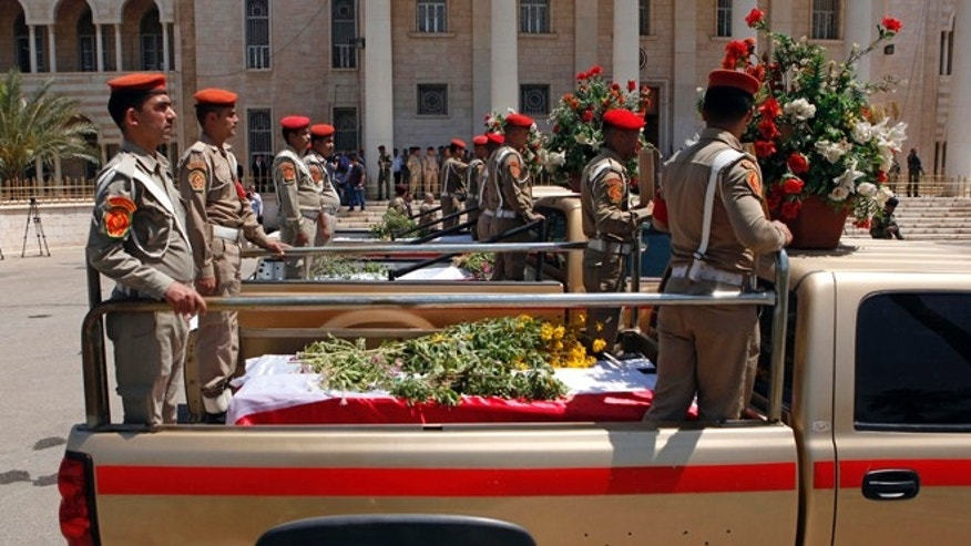 April 28, 2012: Security forces escort the coffins of five slain soldiers at the headquarters of the Iraqi Ministry of Defense in Baghdad, Iraq. Gunmen killed 10 people in Iraq, including five soldiers near the main Sunni protest camp west of Baghdad on Saturday, the latest in a wave of violence that has raised fears the country faces a new round of sectarian bloodshed.