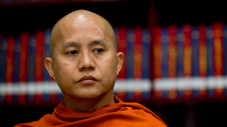 """In this photo taken on March 27, 2013, Buddhist monk Wirathu sits in the library of the Ma Soe Yein monastery during an interview in Mandalay, Myanmar. The popular monk insists he is a man of peace, but has emerged as the spiritual leader of a pro-Buddhist fringe movement accused of fueling a bloody campaign of sectarian violence. Wirathu insists the world has misunderstood him. """"If they knew my true ideas, they would call me savior,"""" he says. (AP Photo/Gemunu Amarasinghe)"""