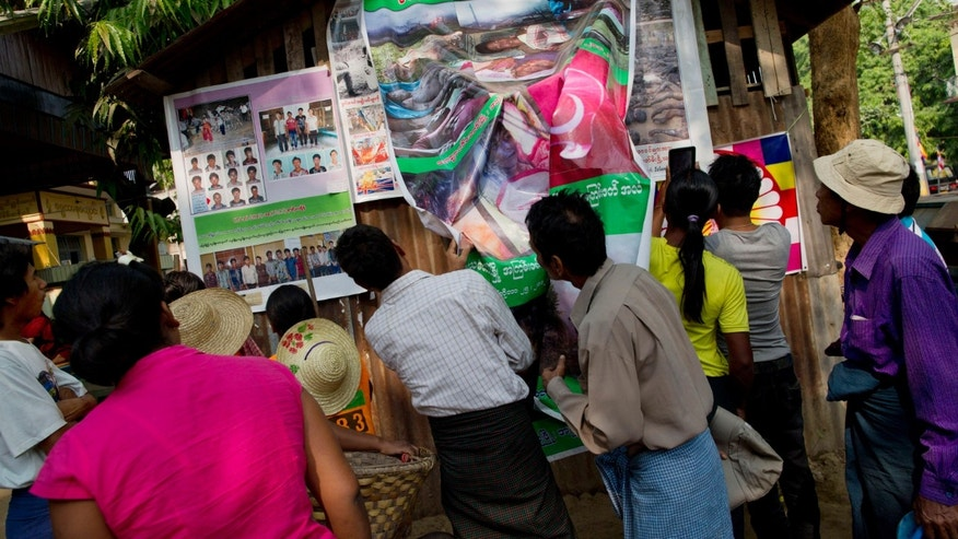 "In this March 28, 2013 photo, visitors to the Ma Soe Yein monastery gather to look at posters displaying the ""969"" logo, right, photos of dead bodies - allegedly Buddhists killed by Muslims, center, and detained illegal Bangladeshi nationals, left, outside the office of Buddhist monk Wirathu in Mandalay, Myanmar.  969 began to coalesce as a political movement after Buddhist-Muslim riots in western Rakhine state last June and October. More than 200 were killed, 70 percent of them Muslim. Over 125,000 remain homeless. (AP Photo/Gemunu Amarasinghe)"