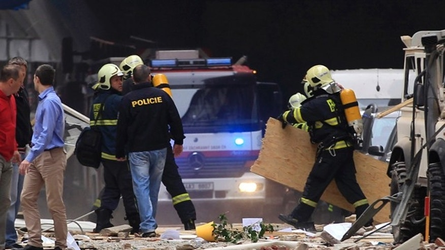 April 29, 2013: Policemen and firefighters inspect a scene of an explosion in downtown Prague, Czech Republic.