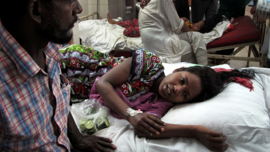 Merina, a survivor of the garment factory building collapse, is comforted by her father in hospital on Saturday April 27, 2013 in Savar, near Dhaka, Bangladesh. Merina was trapped under rubble for three days, surviving with nothing to eat and only a few sips of water. The building collapse was the worst disaster to hit Bangladesh's $20 billion a year garment industry.(AP Photo/Gillian Wong)