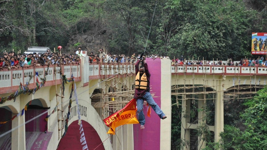 April 28, 2013 -  People watch as Indian Sailendra Nath Roy attempts to cross Teesta river suspended from a zip wire attached to his ponytail moments before his death in Siliguri, West Bengal state, India.