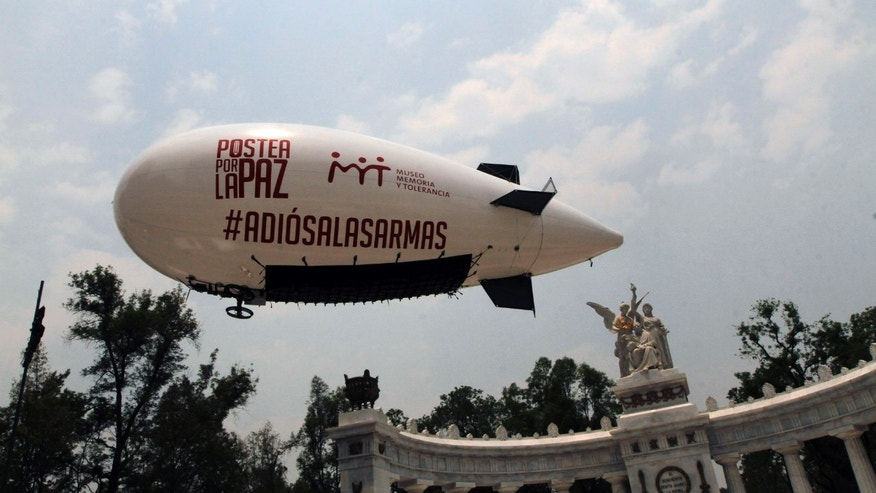 "A blimp with a message that reads in Spanish: ""Post for Peace, #goodbyetoweapons"" flies over the Juarez Monument in Mexico, City, Monday April 29, 2013. The blimp, flown remotely by the Post for Peace organization, attempted to fly to the U.S. Embassy to deliver thousands of signatures condemning the illegal sale of U.S. weapons into Mexico and to contribute to the U.S. gun control debate. The blimp was unable to fly to the embassy due to technical problems but the signatures were eventually delivered by the organizers. (AP Photo/Marco Ugarte)"