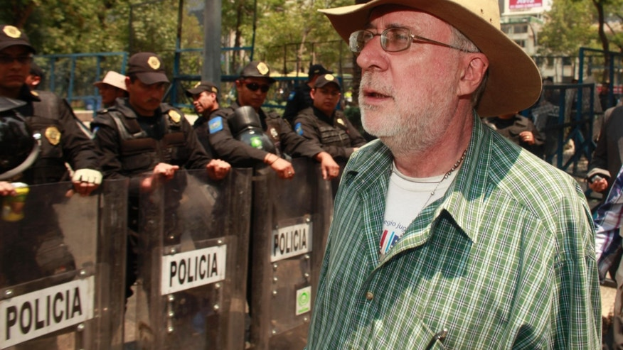 Mexican poet and activist Javier Sicilia walks past riot police as he tries to make his way to the U.S. Embassy to deliver thousands of signatures and a letter in Mexico, City, Monday April 29, 2013. The signatures and the letter, condemning the illegal sale of U.S. weapons into Mexico were supposed to have been flown by a blimp flown remotely by the Post for Peace organization but was unable to fly to the embassy due to technical problems. The signatures were eventually hand delivered by the organizers. (AP Photo/Dario Lopez-Mills)