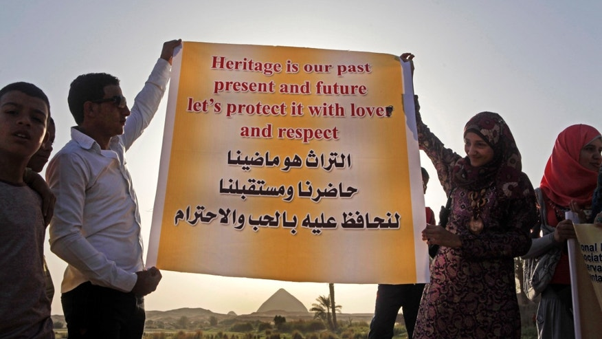 "Egyptian villagers hold a banner in front of the 4,500-year-old ""bent"" pyramid, of Pharaoh Sneferu known for its oddly shaped profile, outside the village of Dahshour, 50 miles (80 Kilometers) south of Cairo, Egypt, Monday, April 29, 2013. Protesters held a rally on Monday against the continued construction of a modern cemetery at the foot of Egypt's first pyramids and its oldest temples. Authorities have so far failed to stop the construction, despite earlier promises to do so. Looting has also spread in the site that has witnessed little excavation, in the absence of security or law enforcement. Arabic on the banner is translated into English at top. (AP Photo/Amr Nabil)"