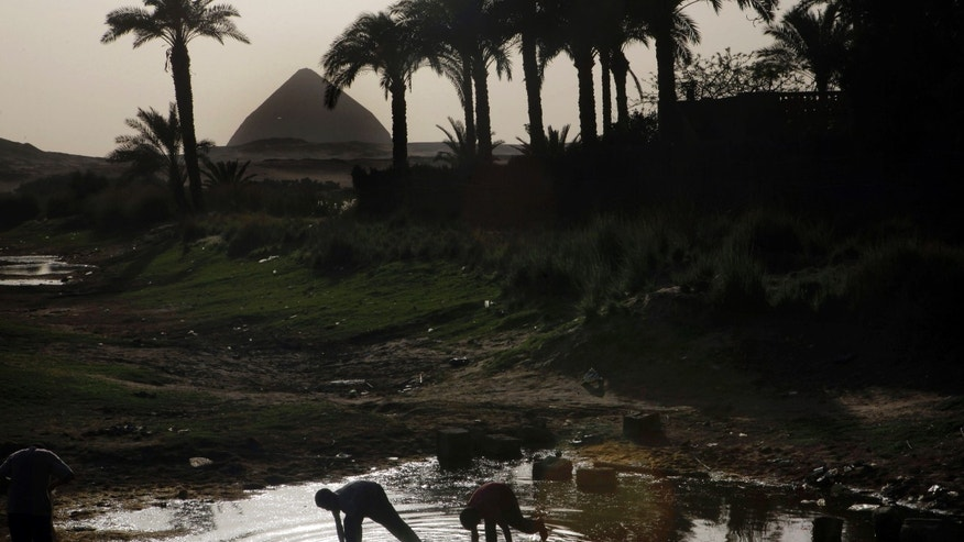 "Egyptian villagers catch lobsters in a pond in front of the historical site of the 4,500-year-old ""bent"" pyramid, of Pharaoh Sneferu known for its oddly shaped profile, outside the village of Dahshour, 50 miles (80 Kilometers) south of Cairo, Egypt, Monday, April 29, 2013. Protesters held a rally on Monday against the continued construction of a modern cemetery at the foot of Egypt's first pyramids and its oldest temples. Authorities have so far failed to stop the construction, despite earlier promises to do so. Looting has also spread in the site that has witnessed little excavation, in the absence of security or law enforcement. (AP Photo/Amr Nabil)"