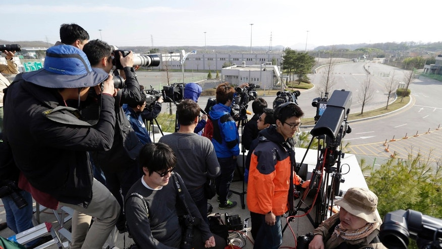 Members of the media wait for South Koreans returning home from North Korea's Kaesong at the customs, immigration and quarantine office near the border village of Panmunjom, that separates the two Koreas, in Paju, north of Seoul, South Korea, Monday, April 29, 2013. South Korea is preparing to pull out its last remaining nationals from a shuttered factory park in North Korea and empty out the complex for the first time since its 2004 opening. (AP Photo/Lee Jin-man)