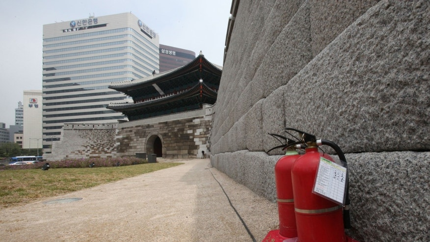"Fire extinguishers are seen at  Sungnyemun gate in Seoul, South Korea, Monday, April 29, 2013. Five years after being torched by a disgruntled elderly man, South Korea's ""No. 1 National Treasure"" is set to reopen, painstakingly restored to its late 14th century glory by a small army of master craftsmen using traditional techniques and tools.(AP Photo/Ahn Young-joon)"