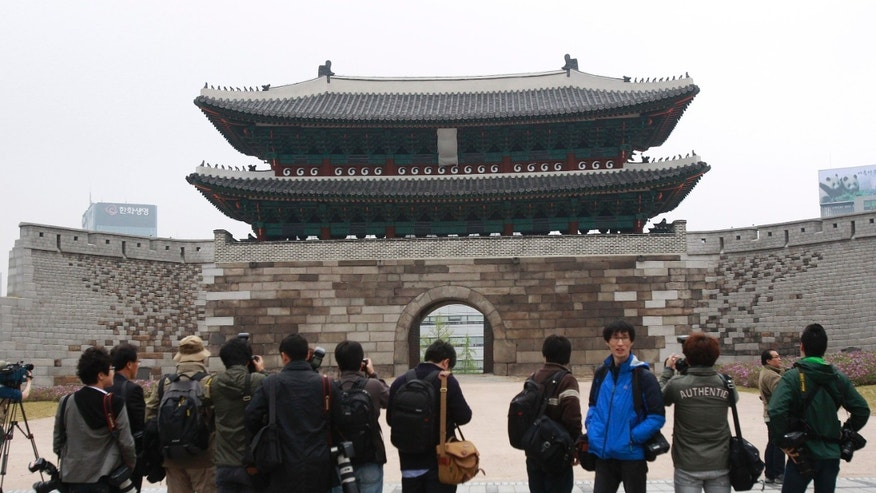 "Photographers take pictures in front of Sungnyemun gate in Seoul, South Korea, Monday, April 29, 2013. Five years after being torched by a disgruntled elderly man, South Korea's ""No. 1 National Treasure"" is set to reopen, painstakingly restored to its late 14th century glory by a small army of master craftsmen using traditional techniques and tools.(AP Photo/Ahn Young-joon)"
