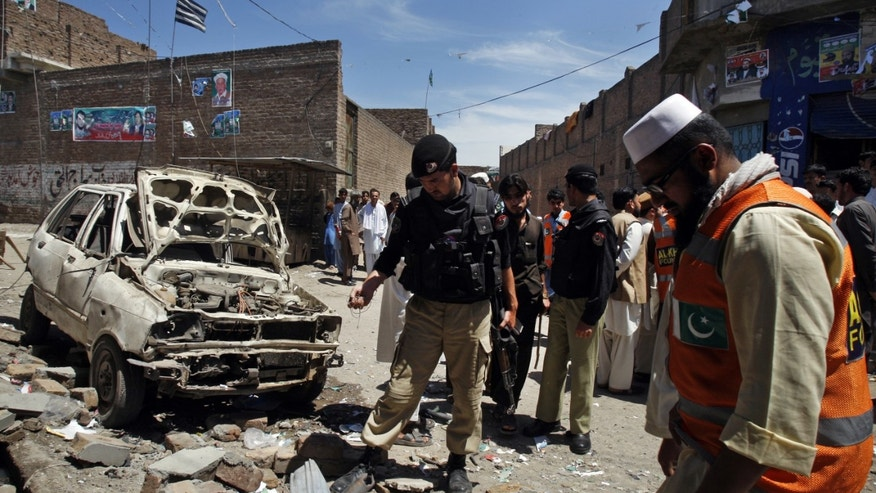 Pakistani police officers and volunteers visit the site of an explosion in Peshawar, Pakistan on Sunday, April 28, 2013. Pakistani Taliban detonated bombs at the campaign offices of two politicians in the country's northwest on Sunday, police said, killing many people in an escalation of attacks on secular, left-leaning political parties. (AP Photo/Mohammad Sajjad)