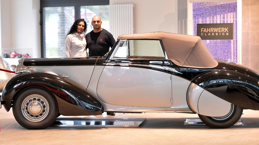 Car saler Sabri Carkan and his wife Saliha stand behind a Daimler DB 18 Drophead Coupe in their showroom in Enger, Germany, Monday, April 29, 2013.  Experts believe the vintage Daimler DB 18 Drophead Coupe is the only one of its kind left. Only eight of these cars were produced since 1939. The rare car was used by Britain's wartime leader Winston Churchill between 1944 and 1949 is being sold on auction site eBay. (AP Photo/Martin Meissner)