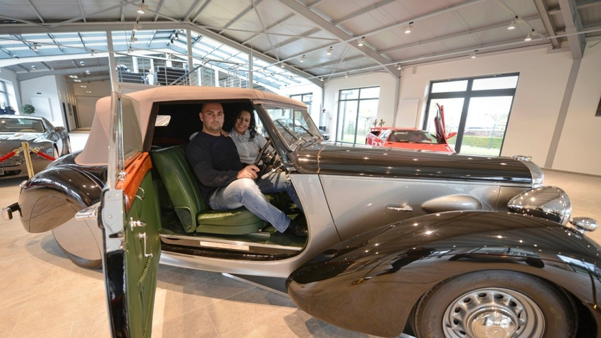 Car saler Sabri Carkan and his wife Saliha is in a Daimler DB 18 Drophead Coupe in their showroom in Enger, Germany, Monday, April 29, 2013,  Experts believe the vintage Daimler DB 18 Drophead Coupe is the only one of its kind left. Only eight of these cars were produced since 1939. The rare car was used by Britain's wartime leader Winston Churchill between 1944 and 1949 is being sold on auction site eBay (AP Photo/Martin Meissner)