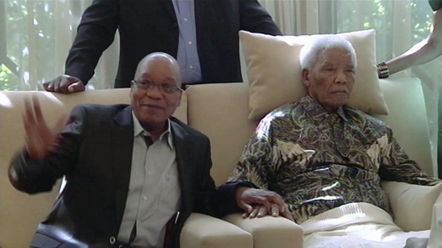 "In this image taken from video, South African President Jacob Zuma, left, sits with the ailing anti-apartheid icon Nelson Madela is filmed Monday April 29, 2013, more than three weeks after being released from hospital. Mandela was treated in hospital for a recurring lung infection.  South African President Jacob Zuma visited the former leader on Monday, but Mandela does not appear to speak during the televised portion of the visit, as he sits in an armchair, his head propped up by a pillow and with his cheeks showing what appear to be marks from a recently removed oxygen mask, although Zuma said he found Nelson Mandela ""in good shape and in good spirits"". (AP Photo/SABC TV) SOUTH AFRICA OUT"