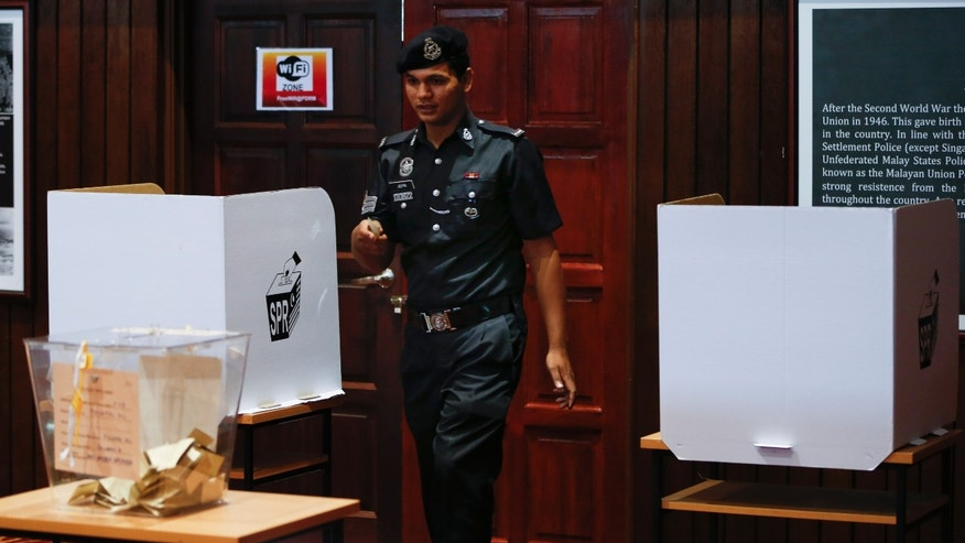 A Malaysian Police officer heads to cast his ballot during the early voting voting for the general elections in Kuala Lumpur, April 30, 2013. Malaysia will hold general elections on May 5 in what could be the toughest test of the ruling coalition's 56-year grip on power in Southeast Asia's third-largest economy. (AP Photo/Vincent Thian)