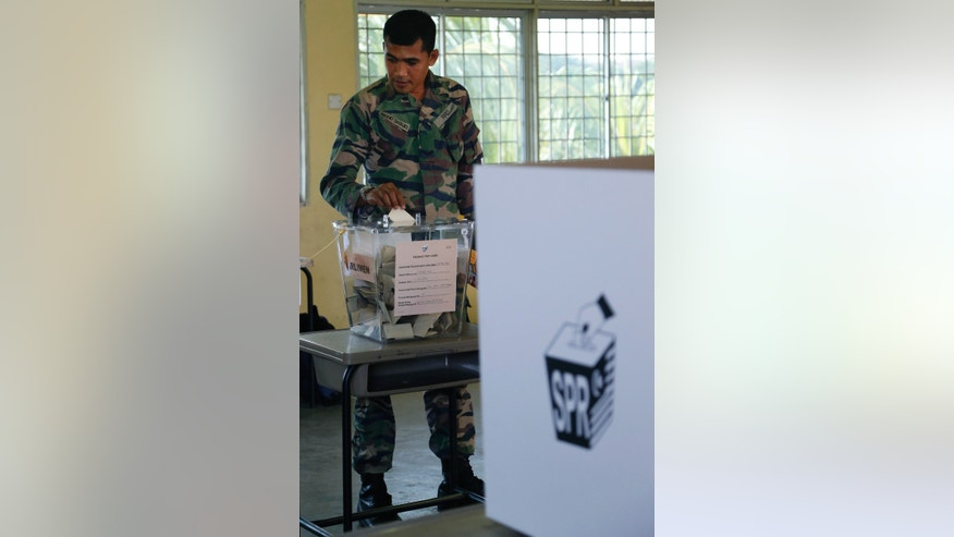 A Malaysian army soldier casts his ballot during the early voting for the general elections in Kuala Lumpur Tuesday, April 30, 2013. Malaysia will hold general elections on May 5 in what could be the toughest test of the ruling coalition's 56-year grip on power in Southeast Asia's third-largest economy. (AP Photo/Vincent Thian)