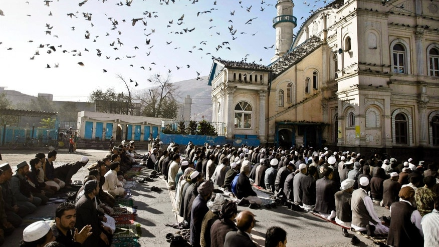 FILE - In this Friday, Oct. 26, 2012 file photo, Afghans listen to preacher while offering the Eid al Adha's prayers outside of Shah-e-Dushamshera mosque in Kabul, Afghanistan. As the country braces for next year's presidential election and the planned withdrawal of most foreign combat troops by the end of 2014, the panel urges the U.S. government and its allies to work harder to promote religious rights in the war-torn nation.  (AP Photo/Musadeq Sadeq, File)