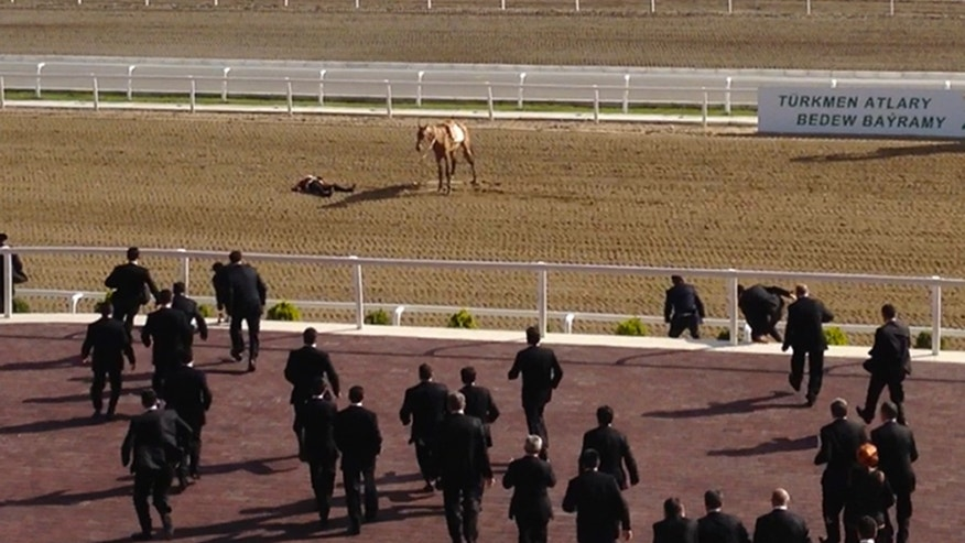 In this image taken Sunday, April 28, 2013 from video footage obtained by APTN, the fifth image taken from a series of 5, guards run to  a man believed to be Turkmen President Gurbanguli Berdymukhamedov lying on the ground after his horse fell throwing him at a horse race during celebrations of  Turkmenistan's renowned desert racehorses  in capital Ashgabat, Turkmenistan. Berdymukhamedov did not appear to have been seriously injured and appeared before the crowd about a half-hour after the fall. (AP Photo/via APTN)