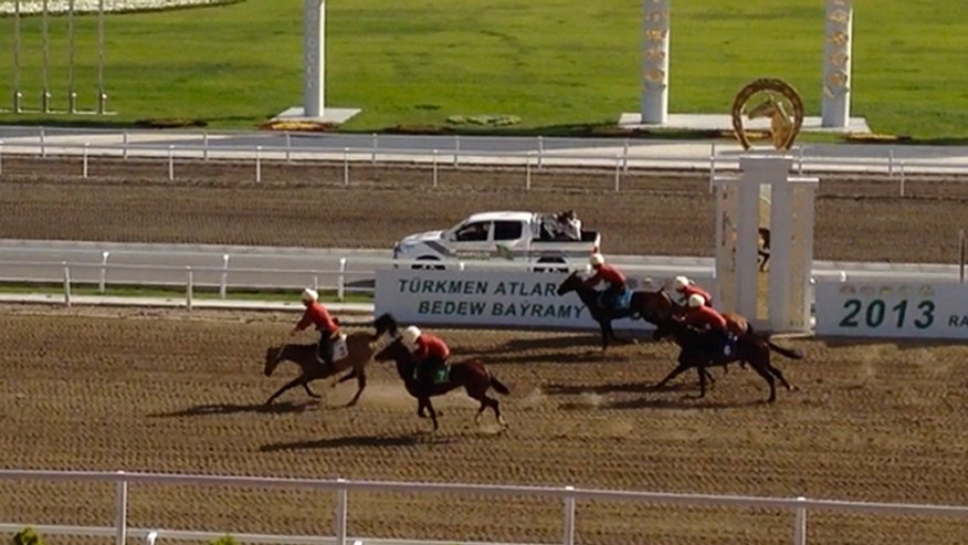 In this image taken Sunday, April 28, 2013 from video footage obtained by APTN, the second image taken from a series of 5,  a man believed to be Turkmen President Gurbanguli Berdymukhamedov rides his horse to victory as his horse starts falling at a  race during celebrations of Turkmenistan's renowned desert racehorses  in capital Ashgabat, Turkmenistan. Berdymukhamedov did not appear to have been seriously injured and appeared before the crowd about a half-hour after the fall. (AP Photo/via APTN)