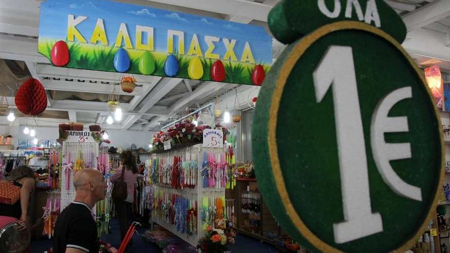 "A one-euro sign and a banner reading ""Happy Easter"" are displayed at a discount store selling candles and other items at the start of Orthodox Holy Week, in Athens, Monday, April 29, 2013. Orthodox Christians around the world celebrate Easter on Sunday, May 5. Retailers and travel agents booking domestic trips are expecting slower sales over the Easter holidays, with a continued recession expected to see Greece's crisis-hit economy contract a further 4.25 percent this year. (AP Photo/Thanassis Stavrakis)"