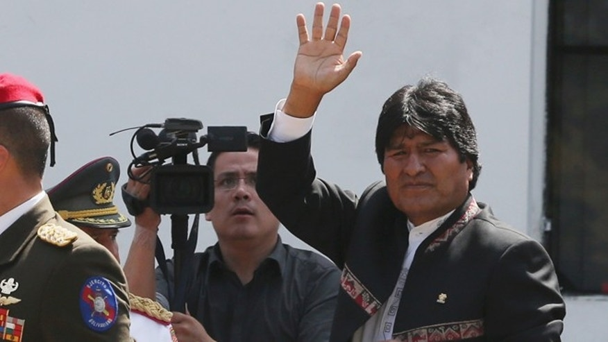 CARACAS, VENEZUELA - MARCH 08:  Bolivian President Evo Morales (R) waves to the crowd while departing the funeral for Venezuelan President Hugo Chavez at the Military Academy on March 8, 2013 in Caracas, Venezuela. Countless Venezuelans have paid their last respects to Chavez and more than 30 heads of state were expected to attend the funeral today.  (Photo by Mario Tama/Getty Images)