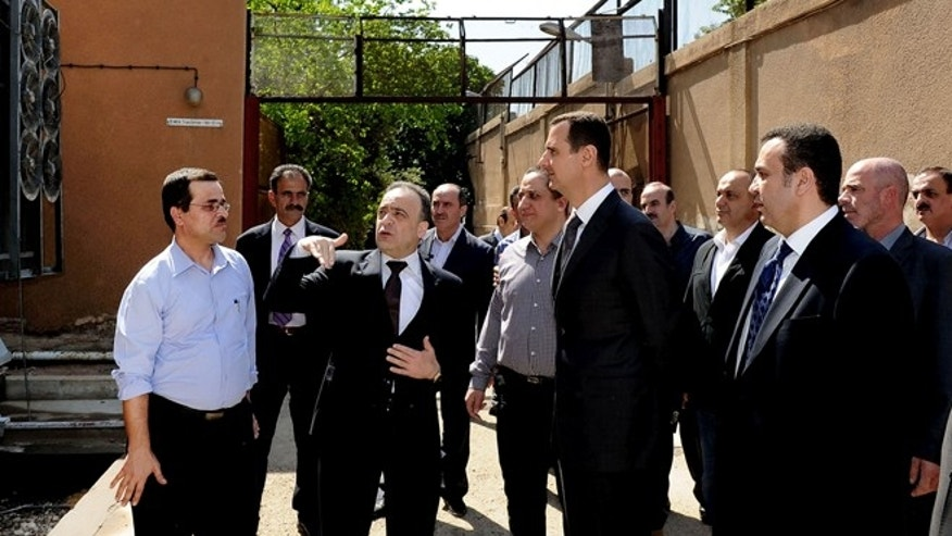 May 1, 2013: In this photo released by the Syrian official news agency SANA, President Bashar Assad, center, visits the Umayyad Electrical Station on May Day, a day after a powerful bomb hit the capital. in Damascus, Syria.