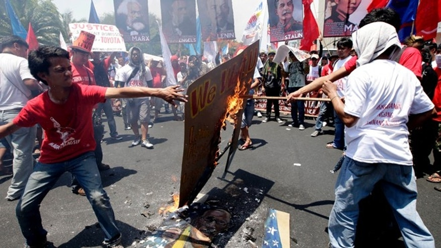 "May 1, 2013: Protesters, mostly workers, burn a mural depicting U.S. President Barack Obama and Philippine President Benigno Aquino III after being blocked by police from getting closer to the U.S. Embassy in Manila to mark International Labor Day in Manila, Philippines. The workers, who have demanding wage increases for years, assailed Aquino for his Labor Day ""gift"" of non-wage benefits."