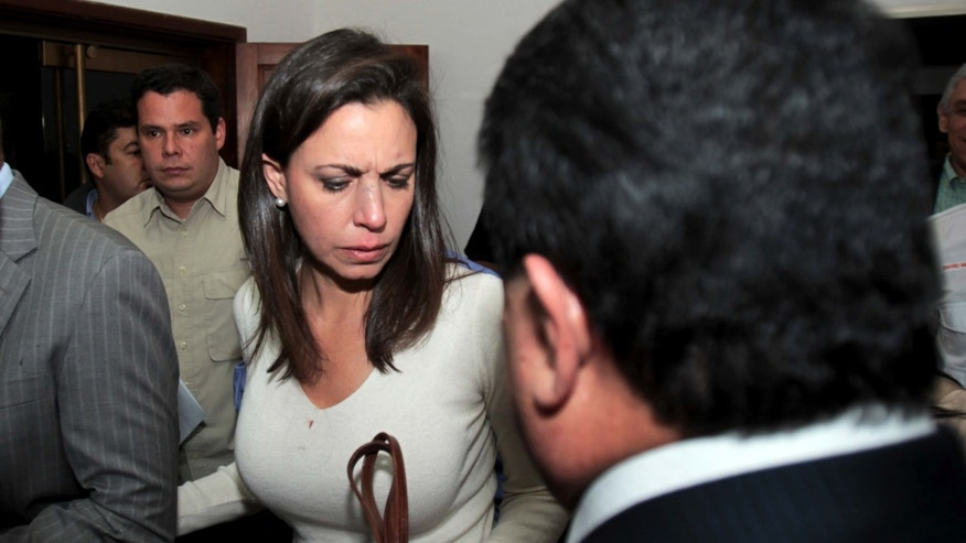 Opposition lawmaker Maria Corina Machado is escorted by party members as she arrives to her political party's headquarters before a press conference in Caracas, Venezuela, Tuesday, April 30, 2013.  Members of Venezuela's National Assembly say post-election tensions set off a brawl Tuesday night between lawmakers that left opposition legislator Julio Borges badly bruised and bleeding, after he and other opposition lawmakers tried to protest a proposal barring them from legislative activities.  The opposition has refused to accept President Nicolas Maduro's narrow April 14 victory, prompting the pro-government side to try to bar them from the assembly. Tuesday's fight was the second in which opposition legislators said the other side attacked them. (AP Photo/Fernando Llano)