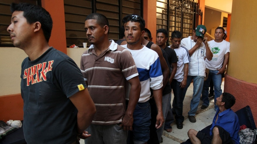 A group of Central American migrants wait in line to call their relatives at a shelter after they were attacked on the freight train they were riding through Mexico, in Acayucan, Mexico, Thursday, May 2, 2013. The United States-bound migrants had hopped on the train in southern Mexico and were traveling through the Gulf Coast state of Veracruz when attackers shot and cut them with machetes. Some jumped from the train to escape and others were thrown off, said migrants' rights activist Tomas Gonzalez Castillo. At least 10 Honduran migrants are recovering from wounds suffered in the attack. (AP Photo/Felix Marquez)