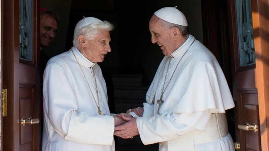 May 2, 2013: In this photo provided by the Vatican newspaper L'Osservatore Romano, Pope emeritus Benedict XVI, left, is welcomed by Pope Francis as he returns at the Vatican from the pontifical summer residence of Castel Gandolfo.