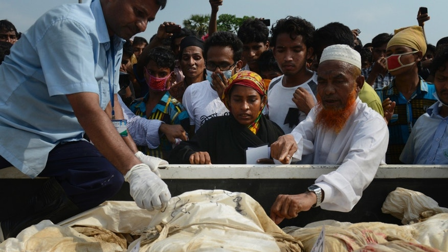 In this photograph taken on Wednesday, May 1, 2013, Farida, center, looks through bodies which arrived at a cemetery in hopes of finding her sister-in-law Fahima in Dhaka, Bangladesh. Just moments before Fahima was to be placed in one of the dozens of unmarked graves dug for victims of Bangladesh's building collapse, Farida was able to claim and leave with her sister-in-law's body. For Farida and countless other relatives of the garment workers who disappeared when Rana Plaza came crashing down, the past week has been one of tumbling expectations, as hope that their loved ones survived faded into the realization that they may have to return home without even a body to bury. (AP Photo/Ismail Ferdous)