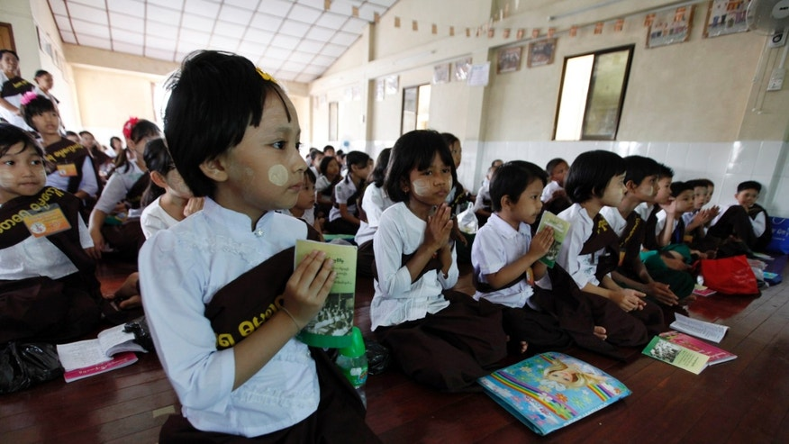 In this photo taken on April 28, 2013, students meditate at a weekly Buddhism religious class in Yangon, Myanmar. The school is one of over 200 affiliated with the 969 movement, which urges Buddhists to shop only in Buddhist shops and not marry, sell property to or hire Muslims. (AP Photo/Khin Maung Win)