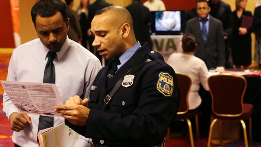 In this Tuesday, Feb. 26, 2013, photo, Philadelphia police recruiting officer Samuel Cruz, right, talks with Ismail Azeer of Carteret, N.J., at the Edison Career Fair job fair in the Iselin section of Woodbridge Township, N.J. (AP Photo/Mel Evans)