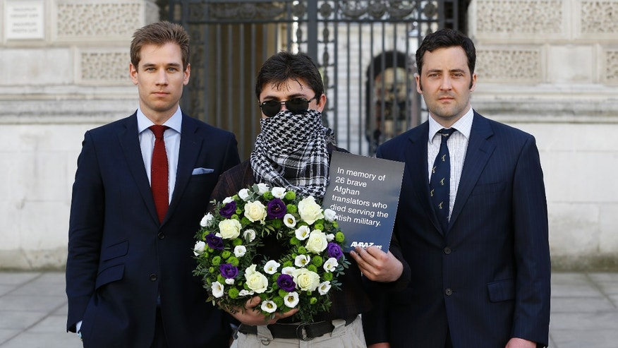"Former British soldiers Patrick Hennessey, left, and Jake Wood, right, and Interpreter ""Mohammad"", centre, hold a wreath outside the Foreign Office in London, Friday, May 3, 2013. Campaigners and two former British soldiers gathered to deliver a box with over 70,000 signatures calling on the UK government to grant Afghan interpreters asylum, a wreath was laid in memory of the 26 Afghan interpreters who have already been killed while serving with British forces. (AP Photo/Kirsty Wigglesworth)"