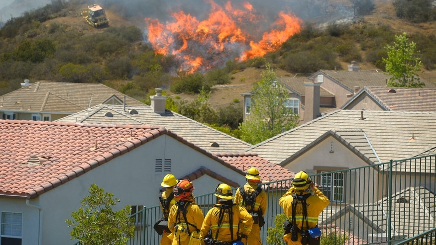 Firefighters from Glendale, Calif., and Pasadena, Calif., stand watch as bulldozers clear a firebreak near a wildfire burning along a hillside near homes in Thousand Oaks, Calif., Thursday, May 2, 2013.