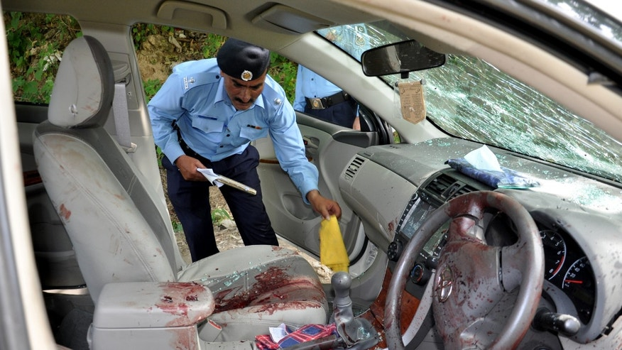May 3, 2013 - A Pakistani police officer examines the car of prosecutor Chaudhry Zulfikar who was targeted by gunmen in Islamabad, Pakistan.
