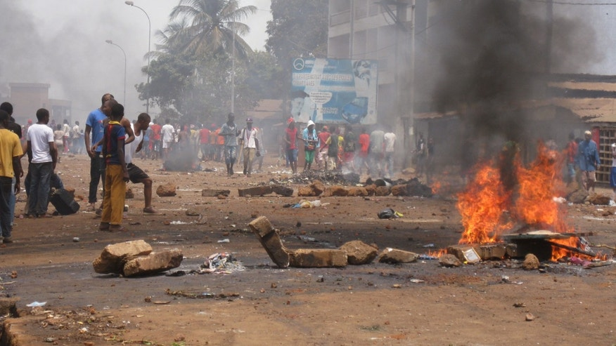 Anti government protesters burn tyres and place rocks in the streets, as they protest against Guinea President Alpha Conde recently announced legislative elections to be held later this year, in Conakry, Guinea, Friday, May 3, 2013.  Ongoing protests have left dead and injured demonstrators as opposition parties accuse President Conde of trying to rig upcoming legislative elections. (AP Photo/Youssouf Bah)