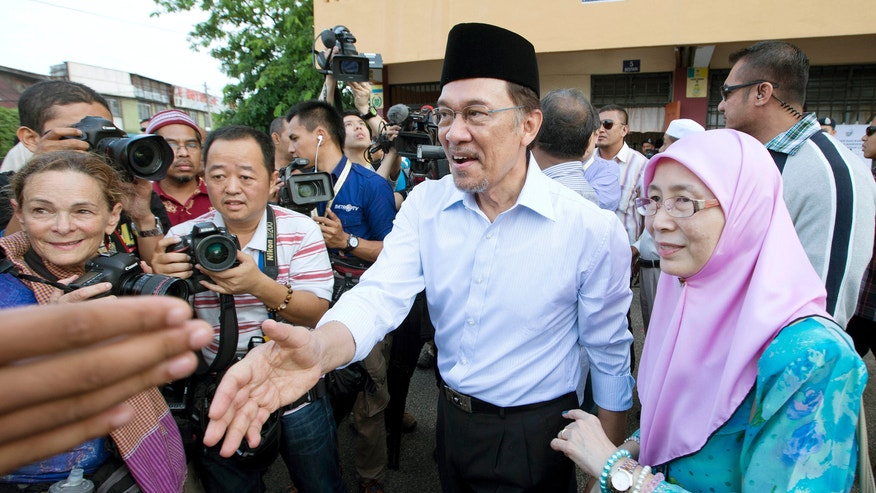 Malaysian opposition leader Anwar Ibrahim, center,  greets supporters with his wife Wan Azizah after voting at Penanti in Penang state in northern Malaysia, Sunday, May 5, 2013. Malaysians have begun voting in emotionally charged national elections that could see the long-ruling coalition ousted after nearly 56 years in power.  (AP Photo/Mark Baker)