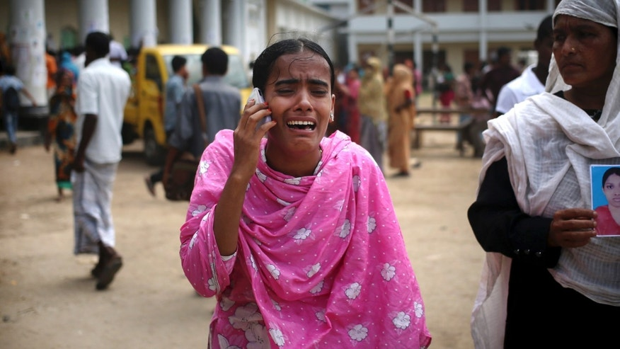 A young lady wails over the phone as she tells her family that she had identified one of the many bodies at a morgue to be her relative, Saturday, May 4, 2013 in Savar, near Dhaka, Bangladesh. In the aftermath of a building collapse that killed more than 530 people, Bangladesh's garment manufacturers may face a choice of reform or perish. (AP Photo/Wong Maye-E)
