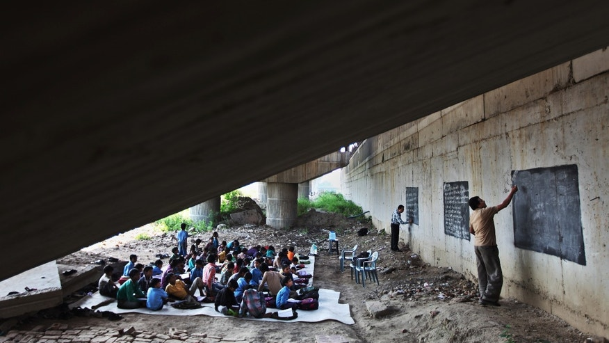 In this April 4, 2013 photo, Rajesh Kumar, the founder of a free school for slum children, second right, and Laxmi Chandra, right, use improvised blackboards to teach pupils under a mass transit bridge in New Delhi, India. Kumar, a shop owner with no formal training, says that education is their only hope. (AP Photo/Altaf Qadri)