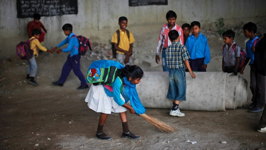 In this April 4, 2013 photo, before the start of class, a girl sweeps a portion of a free makeshift, open-air school run under a mass transit bridge in New Delhi, India. (AP Photo/Altaf Qadri)