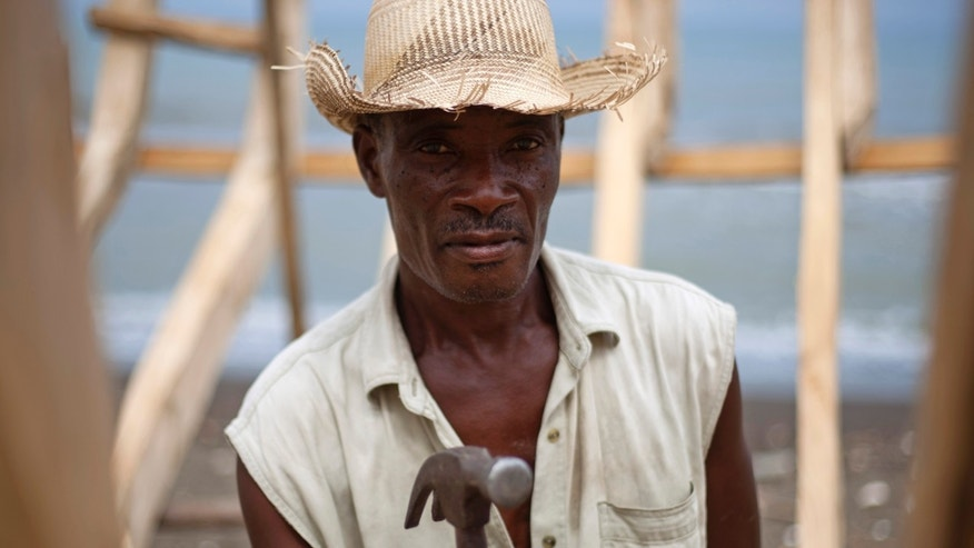 In this May 4, 2013 photo, sailboat builder Audit Volmar, 55, looks at the camera as he hammers the frame of a sailboat as he works on the beach of Leogane, Haiti. The 30-foot-long boats are purchased by smugglers for around $12,000 and then taken to northern Haiti to find passengers. Haitians have fled their troubled country for years, attempting to reach the U.S. or other Caribbean islands by heading north across the open sea or trekking across the island of Hispaniola to scratch out a living in the Dominican Republic. But a newly popular route has caught officials in the Caribbean by surprise, one that is taking migrants to a piece of the U.S. much closer to home: Puerto Rico. (AP Photo/Dieu Nalio Chery)